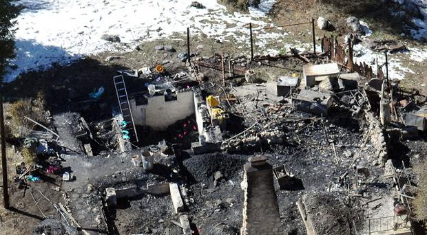 Law enforcement authorities investigate the charred remains of a cabin in the southern California mountains (AP)