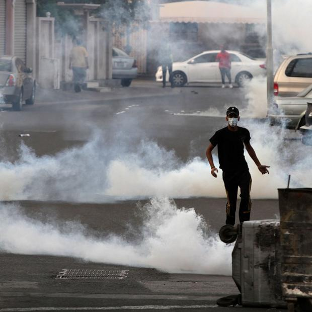 Bahraini anti-government protesters clash with plain clothes police firing tear gas (AP/Hasan Jamali)