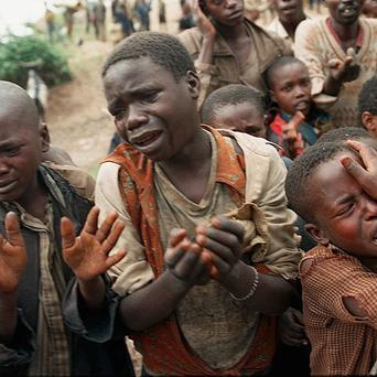 Rwandan refugee children plead with Zairean soldiers to allow them across a bridge separating Rwanda and Zaire during the 1994 genocide (AP, file)