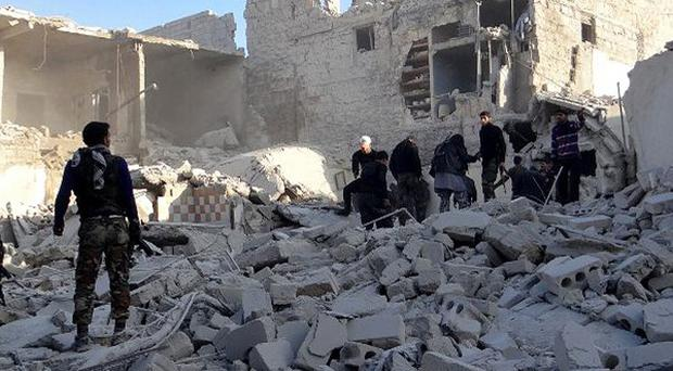 Syrian rebels standing in the rubble of buildings hit by government air strikes near Aleppo International Airport (AP Photo/Aleppo Media Centre AMC)