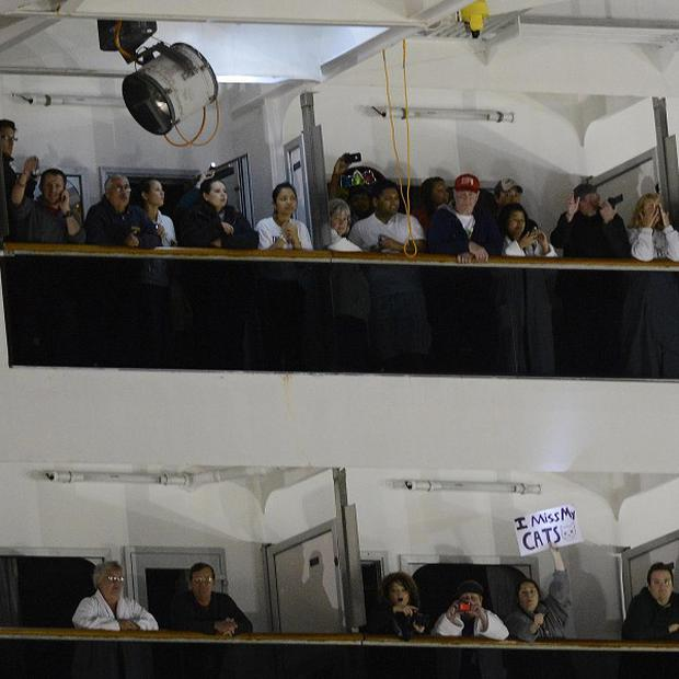 People watch from their balconies and hold up signs aboard the Carnival Triumph after it was towed to the cruise terminal in Mobile, Alabama (AP)