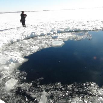 A circular hole in the ice of Chebarkul Lake where a meteor reportedly struck the lake near Chelyabinsk (AP)