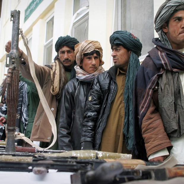 Former Taliban militants turning in their weapons during an amnesty day (AP)