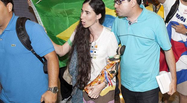 Cuban blogger Yoani Sanchez, centre, is chanted at by pro-Castro supporters, at the Guararapes International airport, Brazil (AP/Hans von Manteuffeul-Agencia O Globo)