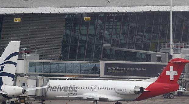Baggage carts make their way past a Helvetic Airways aircraft from which millions of dollars worth of diamonds were stolen at Brussels airport (AP)
