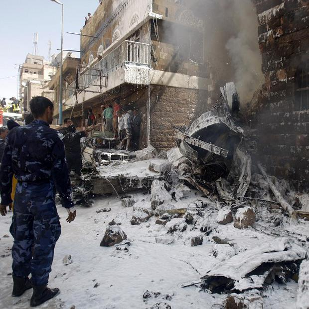 Yemeni security forces look at the impact of a plane crash in Sanaa (AP)