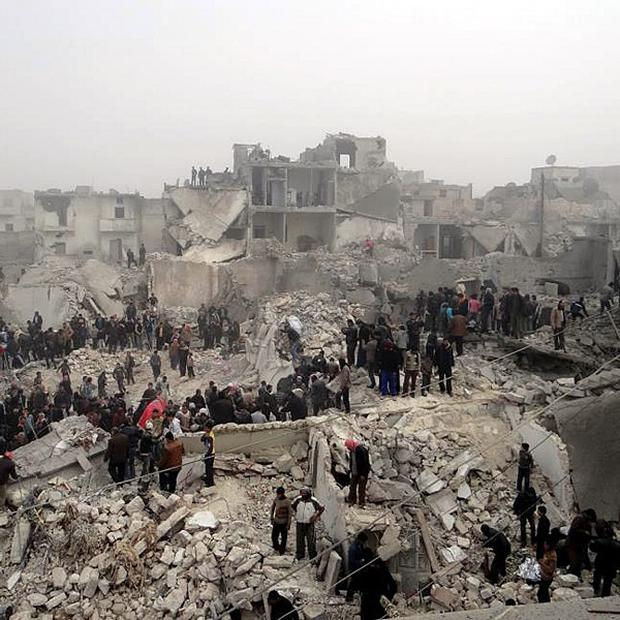 People search through destroyed buildings in the aftermath of a strike by Syrian government forces in Aleppo (AP)