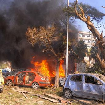 Flames and smoke rise from burned cars after a huge explosion that shook central Damascus (AP/SANA)