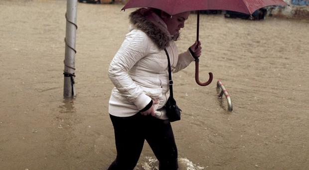 A woman wades across a flooded road linking Athens with its port of Piraeus, during a rainstorm (AP)