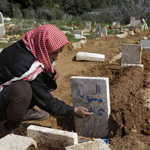 A Syrian villager, Abu Ibrahim, 73, writes the name of his granddaughter on her grave after she was killed in an airstrike by the government (AP)