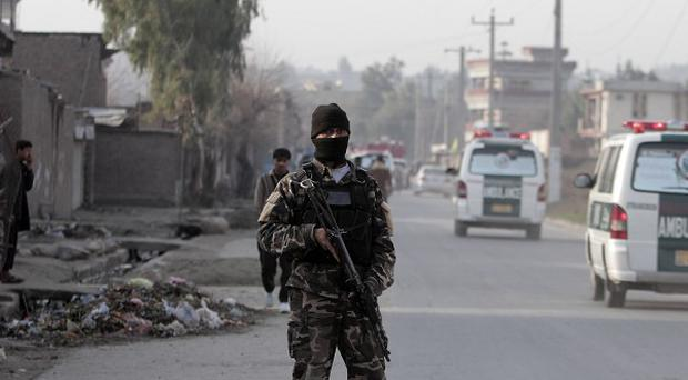 A guard keeps watch at the scene of a suicide car bomb attack which killed several people at the National Directorate of Security in Jalalabad (AP)