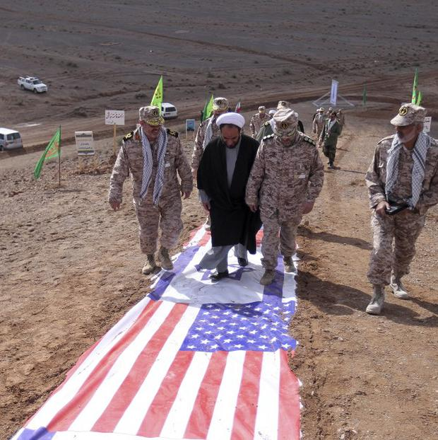 Members of Iran's Revolutionary Guard and a clergyman walk on US and Israeli flags during a drill in Zarand amid escalating tensions between Iran and the West over Tehran's disputed nuclear programme (AP)