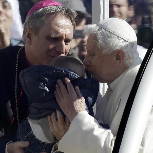 Pope Benedict XVI kisses a baby handed to him by secretary George Ganswein as he greets pilgrims in St. Peter's Square at the Vatican, Wednesday, Feb. 27, 2013. Pope Benedict XVI greeted the Catholic masses in St. Peter's Square Wednesday for the last time before retiring, making several rounds of the square as crowds cheered wildly and stopping to kiss a half-dozen children brought up to him by his secretary. (AP Photo/Gregorio Borgia)