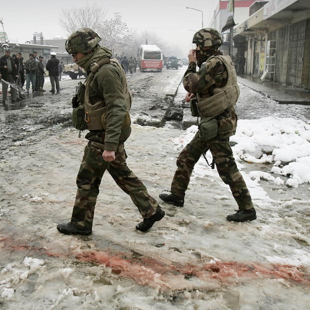 French soldiers with the NATO- led forces walk past blood stained snow at the scene of a suicide attack in Kabul, Afghanistan (AP)