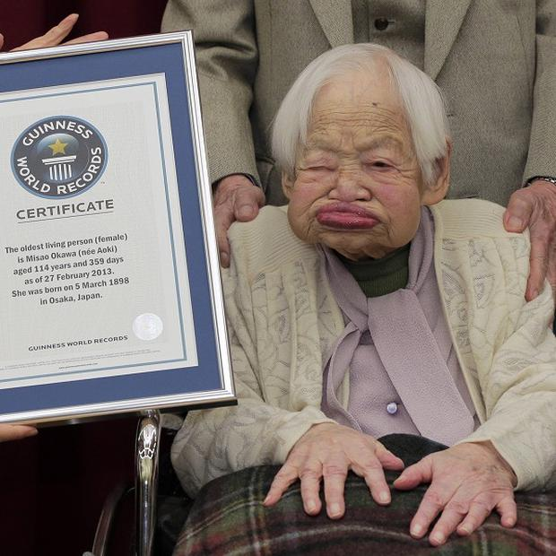 The world's oldest woman - 114-year-old Misao Okawa, from Japan - poses with her certificate from Guinness World Records (AP)
