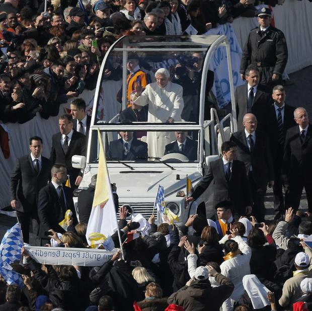 Pope Benedict XVI waves from his pope mobile as he is driven through the crowd during his last general audience in St Peter's Square, the Vatican (AP)