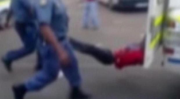 A still from a mobile phone video apparently shows a South African man with his hands tied to a police vehicle as police hold his legs up and the vehicle drives off (South African Daily Sun/AP)