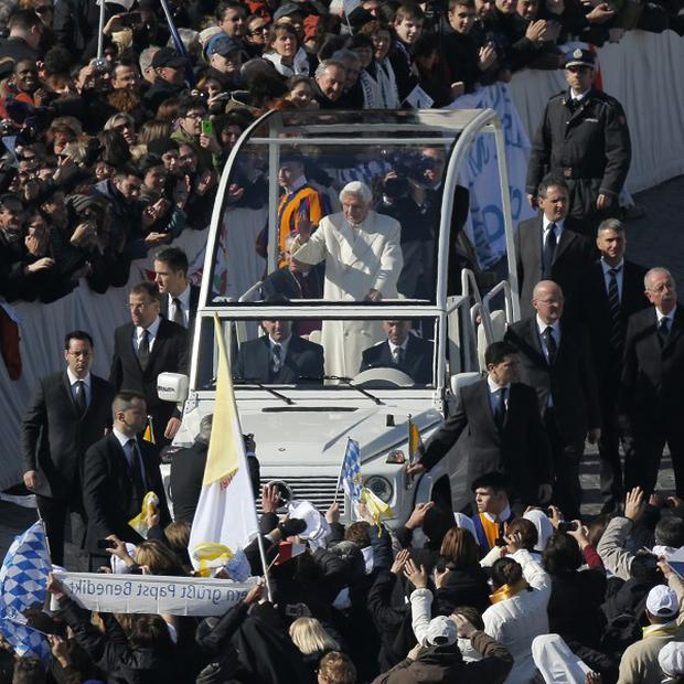 Pope Benedict XVI waves from his pope-mobile as he is driven through the crowd during his last general audience in St Peter's Square (AP)