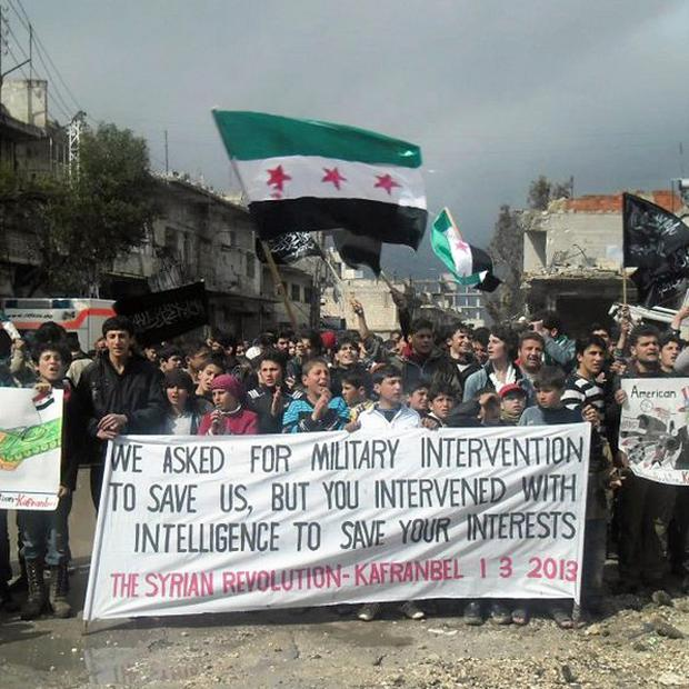 Anti-Syrian regime protesters holding a banner and Syrian revolution flags, during a demonstration, in Idlib province (AP/Edlib News Network)