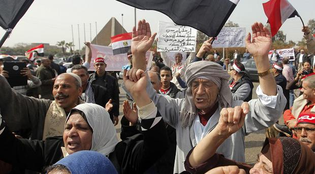 Egyptian pro-military supporters shout anti-Muslim Brotherhood slogans during a protest in front of the unknown soldier, at background left, in Cairo, Egypt, Friday, March 1, 2013. Hundreds of pro-military supporters gathered to reject the Muslim Brotherhood and President Mohammed Morsi's rule calling for the military to return to power. Arabic on red scarves reads, Egypt, and Arabic on banner reads