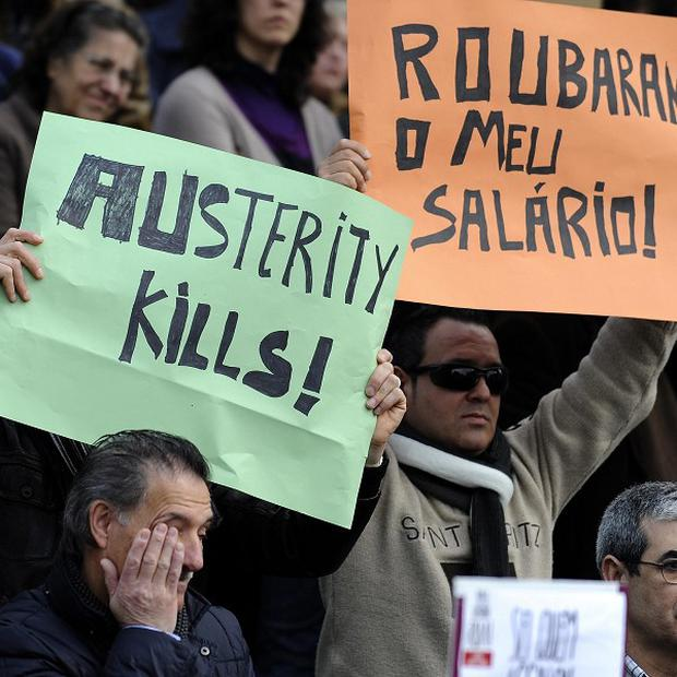 Demonstrators hold banners in a protest against austerity measures applied by Portugal's bailed-out government (AP)