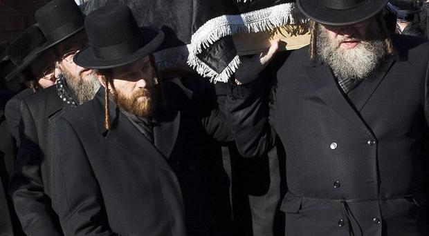 Members of the Satmar Orthodox Jewish community carry the coffins of two expectant parents who were killed in a car accident in New York (AP)