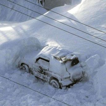 The vehicle of Kazuyo Miyashita pictured after being dug out of the snow along a road in Nakashibetsu, Hokkaido, northern Japan (AP)