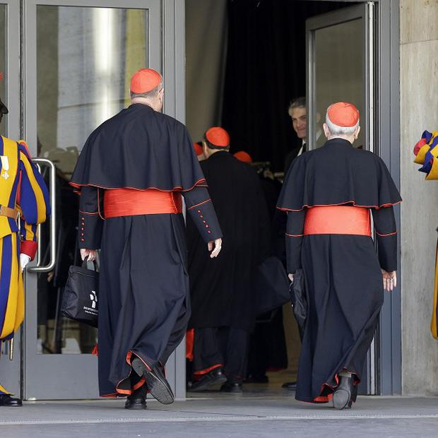 Swiss guards salute as cardinals arrive at the Vatican (AP)