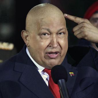 Venezuela's President Hugo Chavez points at his head to show his hair has started to grow back after chemotherapy treatment (AP/Ariana Cubillos)