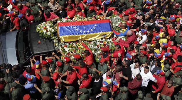 The flag-draped coffin containing the body of Hugo Chavez is taken from the hospital where he died to a military academy (AP)