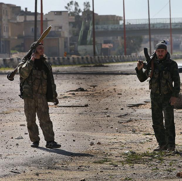 Free Syrian Army fighters patrol in Idlib province (AP)