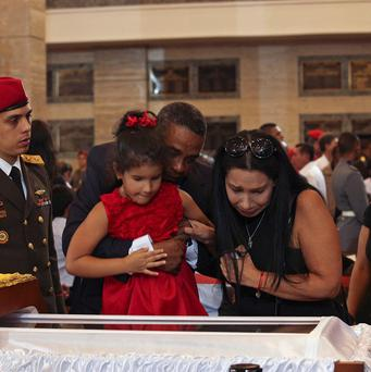 A man helps a girl to look into the glass-topped casket containing the remains of Hugo Chavez (AP/Miraflores Press Office)