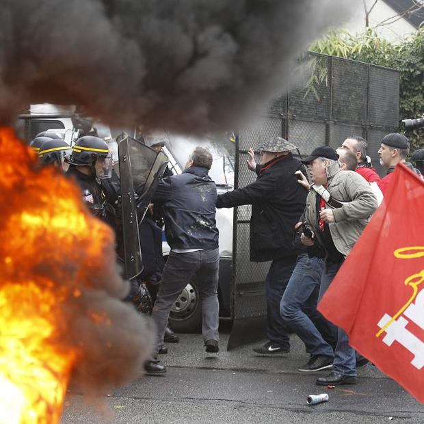 Goodyear workers scuffle with riot policemen during a demonstration against lay-offs in front of the firm's headquarters west of Paris (AP)