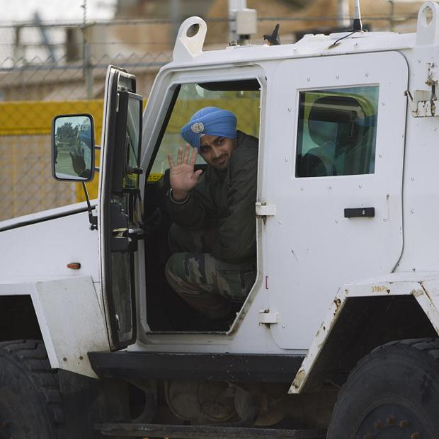 A UN peacekeeper from India leaves the UNDOF Ziouani camp to cross to Syria at the Quneitra Crossing between Syria and the Israeli-controlled Golan Heights (AP)