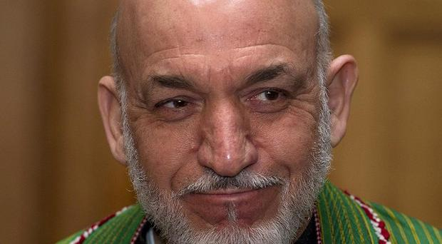 Afghan President Hamid Karzai has accused the Taliban and the United States of working together