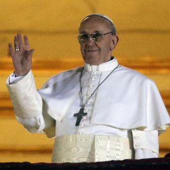 The new pope waves to the crowds from the central balcony of St Peter's Basilica at the Vatican (AP)
