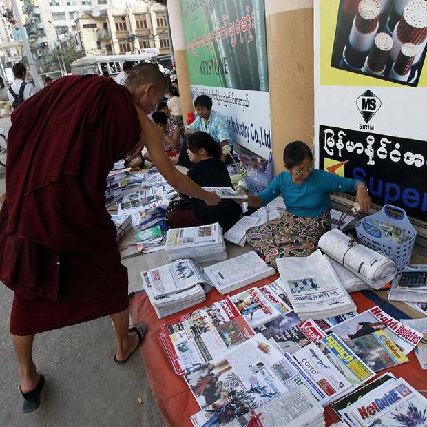 A Buddhist monk buys a state-run newspaper with a report by an investigation commission on an incident at a copper mine, in Burma (AP Photo)