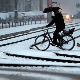A German cyclist gets to grips with the wintry weather (AP)