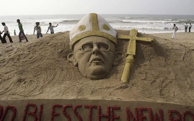 People walk past a sand sculpture of the new pope at the Golden Sea beach on the Bay of Bengal coast in Puri, Orissa state, India (AP)