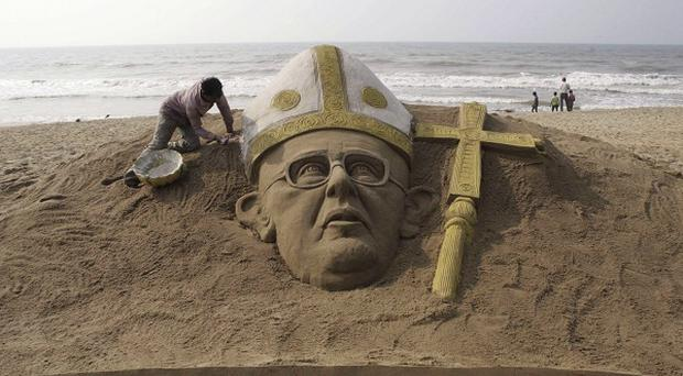 An Indian sand artist finishes a sculpture of the new pope in Puri, Orissa state, India (AP)