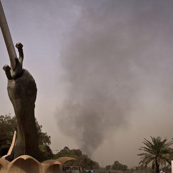 Black smoke from a car bomb attack rises into the sky behind the Crossed Swords monument in Baghdad (AP)