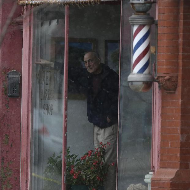 A man watches from the window of a barber shop in Herkimer before police shot dead a gunman suspected of killing four people (AP)