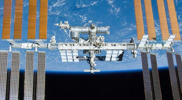 The return of three astronauts from the International Space Station has been delayed by bad weather
