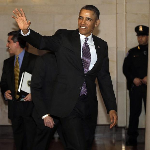 President Barack Obama waves to members of the media as he heads to a meeting with House Democratic Caucus (AP)