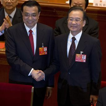 Newly named Chinese Premier Li Keqiang, left, shakes hands with former Chinese Premier Wen Jiabao (AP)