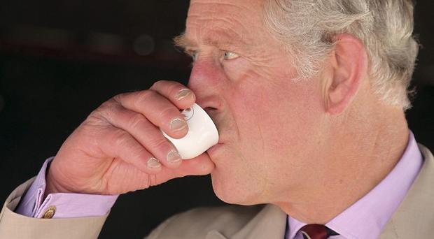 Prince Charles drinks a traditional Arabic coffee during his visit to the Al Safwa Farm in Doha, Qatar (AP)