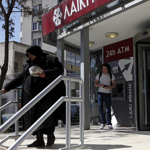 An elderly woman leaves the bank as another man leaves the ATM machine in Nicosia, Cyprus (AP)