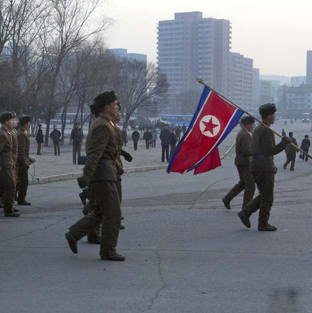 North Korean soldiers led by their national flag bearers, march on a street in Pyongyang (AP)