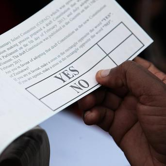 An election official holds one of the ballot papers for use during a referendum in Harare, Zimbabwe (AP)