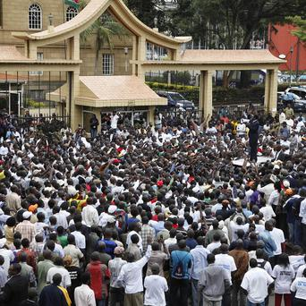 Supporters of Prime Minister Raila Odinga gather outside the Kenyan Supreme Court (AP)
